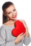 Porträt der schönen herrlichen lächelnden Frau mit hellem Make-up des Zaubers und rotem Herzen in der Hand Stockfoto