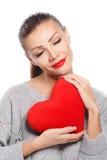 Porträt der schönen herrlichen lächelnden Frau mit hellem Make-up des Zaubers und rotem Herzen in der Hand Lizenzfreie Stockfotografie