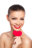 Porträt der schönen herrlichen lächelnden Frau mit hellem Make-up des Zaubers und rotem Herzen in der Hand Stockbilder
