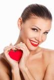 Porträt der schönen herrlichen lächelnden Frau mit hellem Make-up des Zaubers und rotem Herzen in der Hand Lizenzfreie Stockbilder