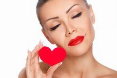Porträt der schönen herrlichen lächelnden Frau mit hellem Make-up des Zaubers und rotem Herzen in der Hand Lizenzfreies Stockfoto