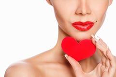 Porträt der schönen herrlichen lächelnden Frau mit hellem Make-up des Zaubers und rotem Herzen in der Hand Lizenzfreies Stockbild