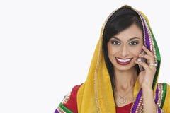 Porträt der schönen indischen Frau in antwortendem Telefonanruf der traditionellen Abnutzung über weißem Hintergrund lizenzfreies stockbild