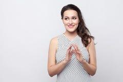 Porträt der schönen jungen brunette Frau des toothy smiley mit Make-up und gestreifter Kleiderstellung und weg schauen mit schlau lizenzfreies stockfoto