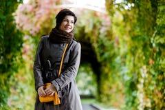 Porträt der schönen jungen Brunettefrau, die im belaubten Bogen aufwirft lizenzfreie stockfotografie