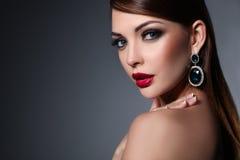 Porträt der schönen jungen Brunettefrau im Ohr stockbild