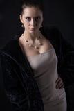 Porträt der Frau mit Schmuck im langen schwarzen Pelzluxusmantel Stockfotografie