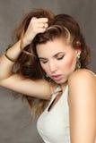 Porträt der schönen jungen Frau auf einem grauen Hintergrund stockfoto