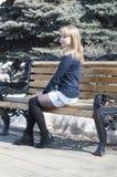 Porträt der schönen jungen Frau auf einer Bank im Park lizenzfreie stockfotos
