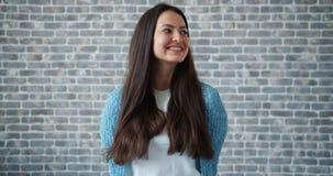 Porträt der schönen jungen Frau, die auf Backsteinmauerhintergrund lächelt stock footage