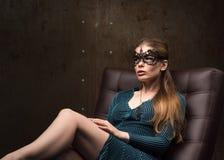 Porträt der schönen jungen Frau, die auf der Couch sitzt Schauen Sie vorsichtig lizenzfreie stockfotografie