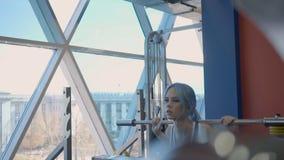 Porträt der schönen jungen Frau, die Barbellhocken in der Energiezone der modernen Turnhalle tut stock footage