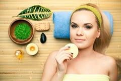 Porträt der schönen jungen Frau, die ihr Gesicht mit Schwamm berührt lizenzfreies stockfoto