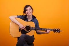 Porträt der schönen jungen Frau, die im Studio mit Gitarre über gelbem Hintergrund lächelt lizenzfreies stockfoto