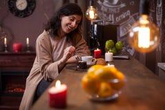 Porträt der schönen jungen Frau, die Kuchen am Barzähler in einer Kaffeestube isst stockbilder