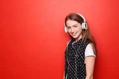 Porträt der schönen jungen Frau, die Musik gegen Farbhintergrund hört lizenzfreie stockbilder