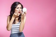 Porträt der schönen jungen Frau, die Pickel beim Betrachten des Spiegels zusammendrückt lizenzfreies stockfoto