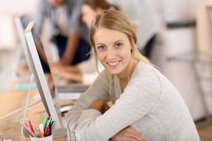 Porträt der schönen jungen Frau, die am Schreibtisch sitzt stockfotos