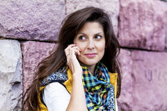 Porträt der schönen jungen Frau, die am Telefon im Freien spricht Lizenzfreie Stockfotos