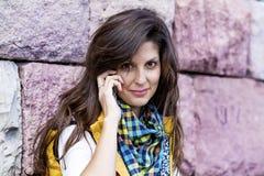 Porträt der schönen jungen Frau, die am Telefon im Freien spricht Lizenzfreie Stockbilder