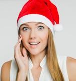 Porträt der schönen jungen Frau, die Weihnachtsmann-Hut trägt Lizenzfreies Stockfoto