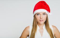 Porträt der schönen jungen Frau, die Weihnachtsmann-Hut trägt Lizenzfreies Stockbild