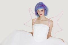 Porträt der schönen jungen Frau gekleidet als Engel mit dem gefärbten Haar gegen grauen Hintergrund Lizenzfreies Stockbild