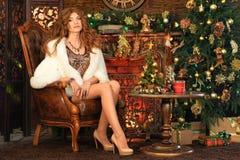 Porträt der schönen jungen Frau im Pelzmantelsitzen stockbild