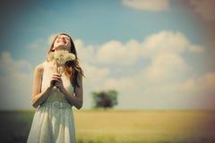 Porträt der schönen jungen Frau mit Bündel Löwenzahn auf Th Stockfotografie