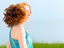 Porträt der schönen jungen Frau mit dem flatternden roten Haar Lizenzfreie Stockfotografie