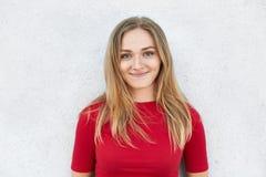 Porträt der schönen jungen Frau mit dem geraden blonden Haar, den warmen grünen Augen und den Grübchen auf ihren Backen, die rote stockfotos