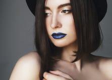 Porträt der schönen jungen Frau mit den blauen Lippen und im Hut bea Lizenzfreie Stockfotografie