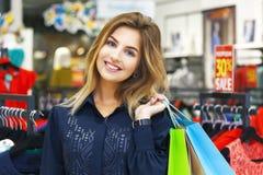 Porträt der schönen jungen Frau mit Einkaufstaschen in der Kleidung stockbild