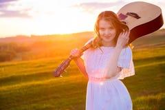 Porträt der schönen jungen Frau mit Gitarre auf dem Gebiet Stockbild
