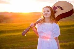 Porträt der schönen jungen Frau mit Gitarre auf dem Gebiet Stockbilder