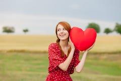 Porträt der schönen jungen Frau mit Herzen formte Spielzeug auf dem w Stockbilder