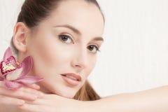 Porträt der schönen jungen Frau mit rosa Orchidee Stockbilder
