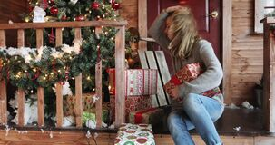 Porträt der schönen jungen Frau mit Untersuchungsgeschenkboxen des langen Haares auf einem Portal des Hauses stock footage