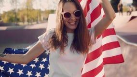 Porträt der schönen jungen Frau in der Sonnenbrille, die amerikanische Flagge beim im Rochenpark stolz lächeln hält freundlich stock footage