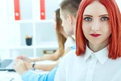 Porträt der schönen jungen Geschäftsfrau mit den Paarangestellten, die im Hintergrund arbeiten Ernstes Geschäft und Partnerschaft Lizenzfreies Stockfoto
