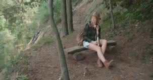 Porträt der schönen kaukasischen Frau, die auf Holzbank in einem Wald sitzt stock video footage