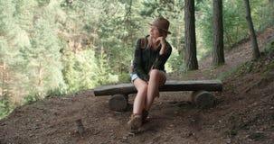 Porträt der schönen kaukasischen Frau, die auf Holzbank in einem Wald sitzt Lizenzfreies Stockbild