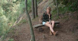 Porträt der schönen kaukasischen Frau, die auf Holzbank in einem Wald sitzt Stockfoto