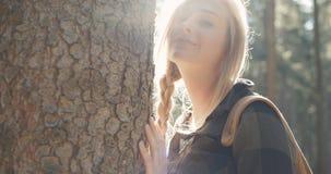 Porträt der schönen kaukasischen Frau, die durch einen Baum aufwirft stock video