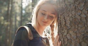 Porträt der schönen kaukasischen Frau, die durch einen Baum aufwirft stock footage