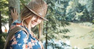Porträt der schönen kaukasischen Frau, die zu einer Kamera in einem Wald lächelt Stockbilder