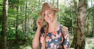 Porträt der schönen kaukasischen Frau in einem Waldtragenden Hut lächelnd zu einer Kamera Stockfotografie