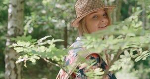 Porträt der schönen kaukasischen Frau in einem Waldtragenden Hut, der in einem Wald sich entspannt Stockfotografie