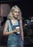 Porträt der schönen kaukasischen jugendlichen jungen blonden Mädchenfrau des alternativen Modells im blauen T-Shirt, Jeansspielan Stockfotografie