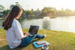 Porträt der schönen lächelnden Frau, die auf grünem Gras im Park mit den Beinen gekreuzt während des Sommertages sitzt und Anmerk stockfoto